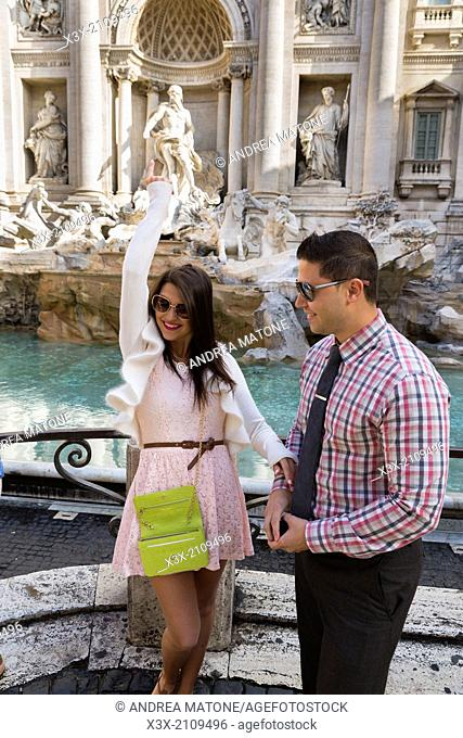 Couple throwing a coin in the Trevi fountain. Rome, Italy