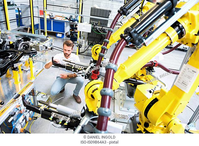 Young male engineer testing machinery in engineering factory