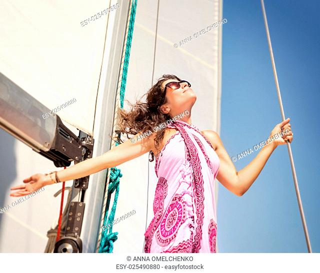 Happy woman having fun on sailboat, looking up in the sky with raised hands and enjoying bright sunny day, active summer vacation