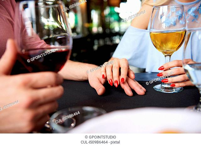 Cropped view of woman's hand on boyfriend's hand at restaurant table