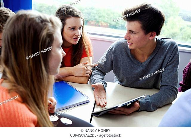 Teenage schoolchildren sitting at desk using digital tablet