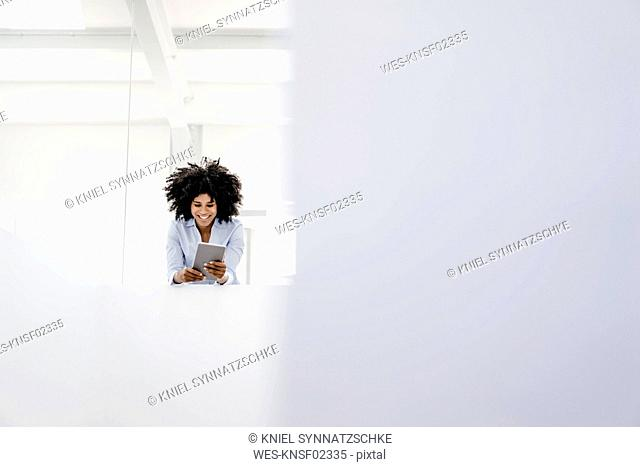 Smiling young woman using tablet in office