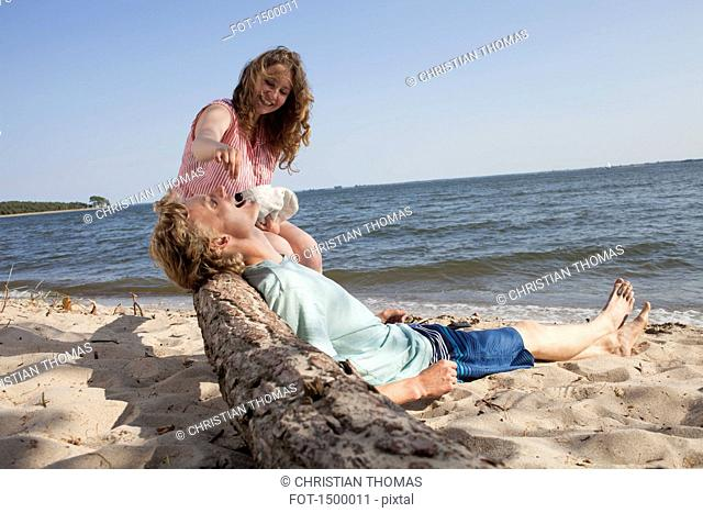 Happy friend feeding cherry to man while relaxing at beach