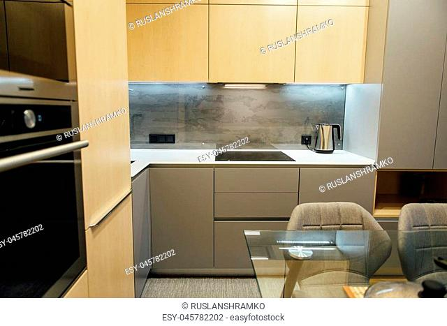 Modern kitchen with wooden furniture with glass elements and wooden floor