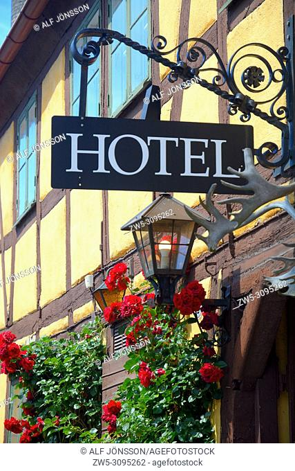 Hotel facade with roses, lamp and sign at an old house in Ystad, Scania, Sweden