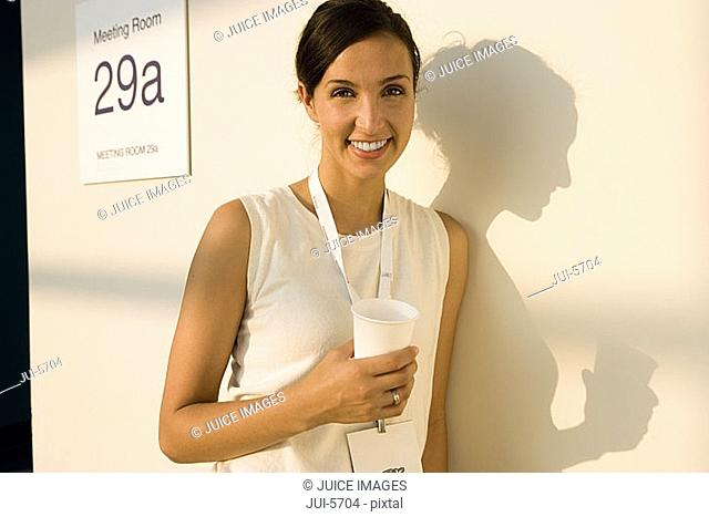Businesswoman standing outside meeting room, taking coffee break, casting shadow on wall, smiling, portrait