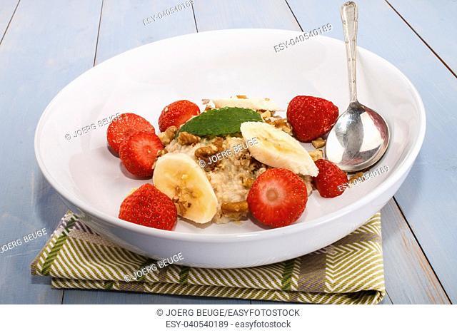 healthy breakfast with porridge, walnut, strawberry and mint leaf