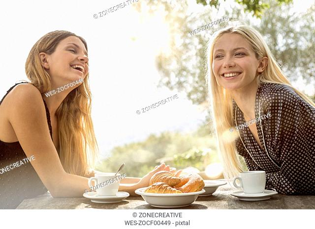 Two laughing friends at breakfast table in the morning