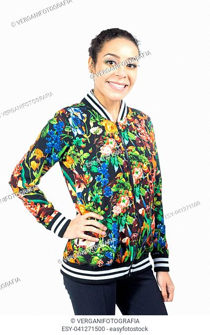 Young woman with haired hair is posing for the photos. The hand is resting on the waist. Ethnic girl wearing colorful floral pattern jacket