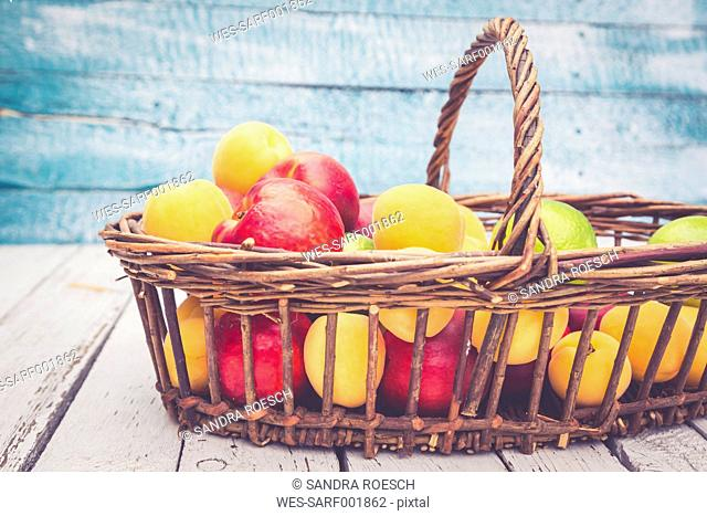 Wickerbasket of limes, apricots and nectarines