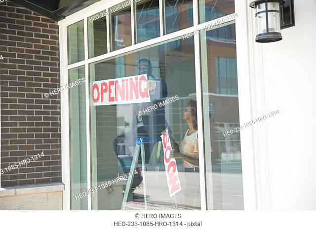 Business owners hanging Opening sign in shop window