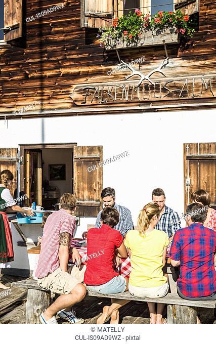 Friends having breakfast outside chalet, Tyrol, Austria