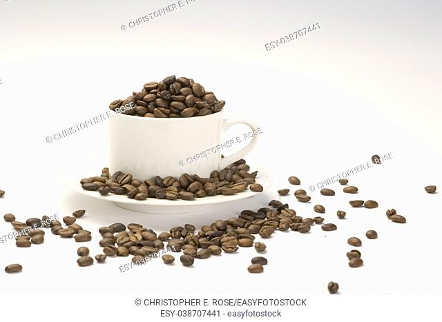 Coffee beans in a white cup and saucer on a plain background