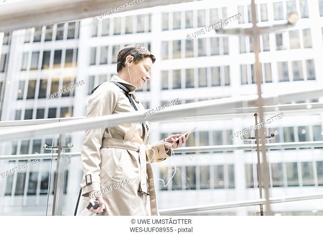 USA, New York City, businesswoman on the go with cell phone and earphones
