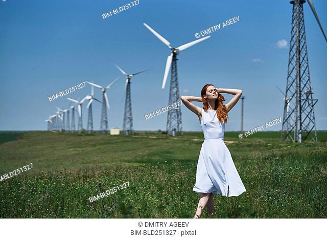Caucasian woman in field near wind turbines