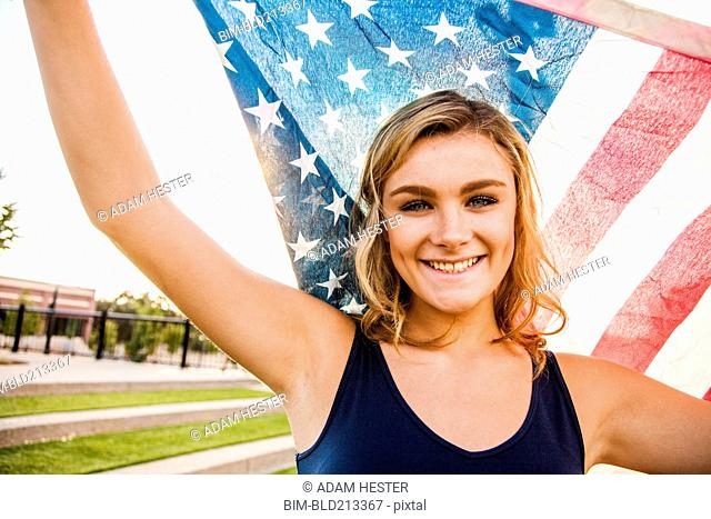 Caucasian teenage girl holding American flag
