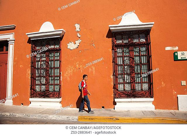 Young man walking in the street at the historic center in front of colonial buildings, Campeche, Campeche State, Mexico, Central America