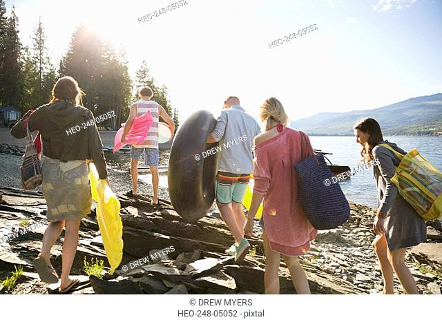 Young friends carrying pool rafts at sunny lakeside