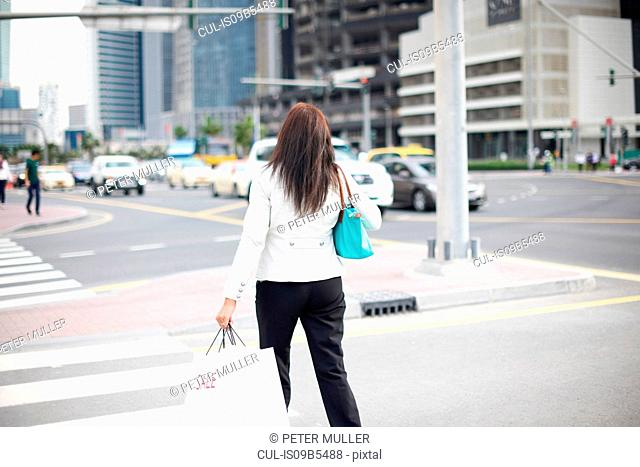 Rear view of woman with shopping bags strolling along street, Dubai, United Arab Emirates