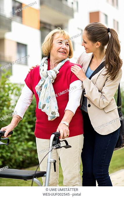 Granddaughter assisting her grandmother walking with wheeled walker