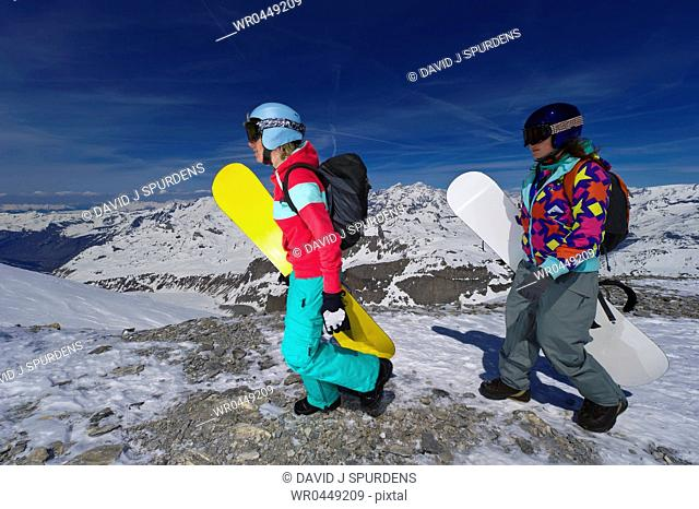 Two female snowboarders walk to the mountains edge