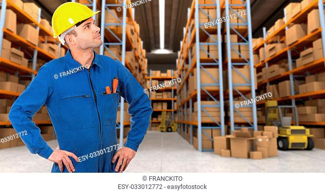 Man with helmet and blue overalls in a distribution warehouse