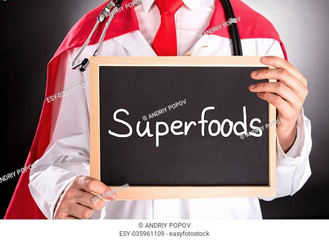 Close-up Of Superhero Doctor Holding Small Chalkboard With The Text Superfoods