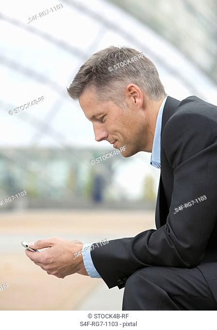 Businessman with cell phone, side view