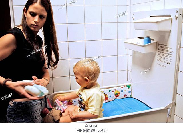 Mutter wickelt einjaehrige Tochter. - Niederoesterreich, Ísterreich, 09/08/2007
