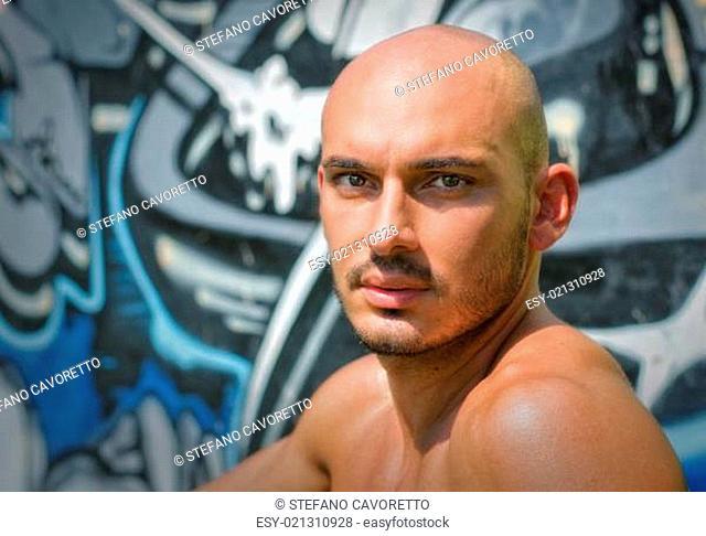 Headshot of bald young man shirtless outdoors