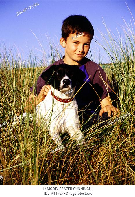 A boy sitting in the grass with his dog