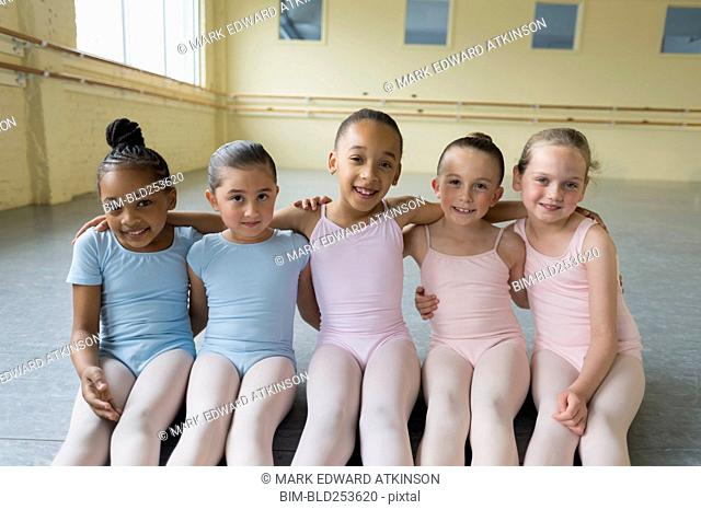 Portrait of smiling girls hugging on floor of ballet studio