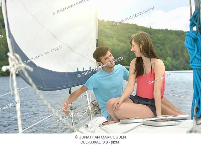 Young couple sailing on sunlit yacht over lake, smiling