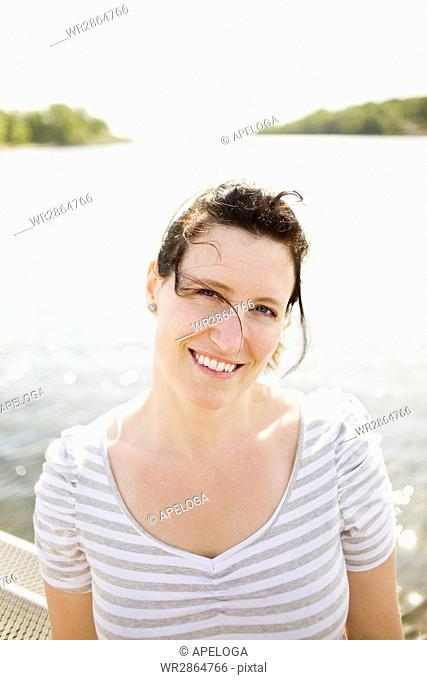 Portrait of happy woman standing against river on sunny day