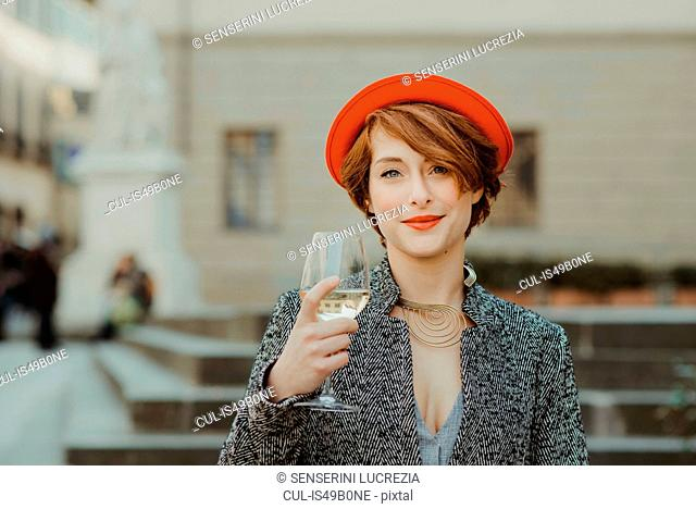 Portrait of young woman, outdoors, holding glass of wine