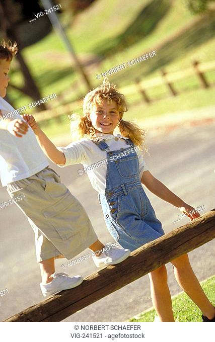 park-scene, portrait, full-figure, 10-year-old blond curly girl with plaits wearing jeans helps her younger brother crossing a beam with her hand  - GERMANY