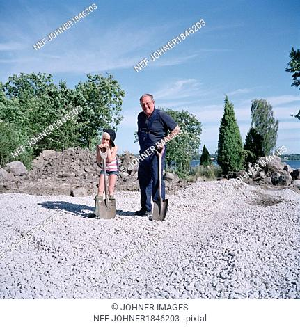 Girl with grandfather standing with spades