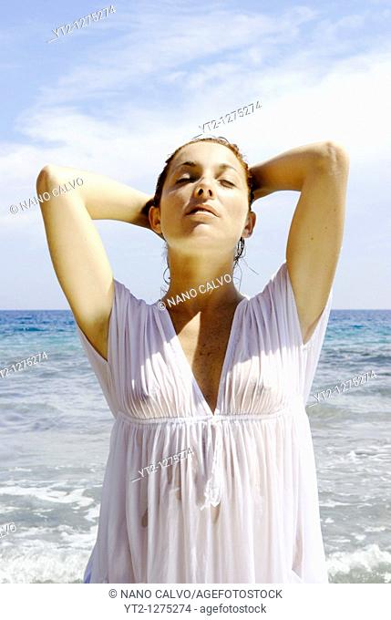Portrait of a cute and natural looking red haired girl posing on the beach, inside water, with a wet white dress, Ibiza, Spain