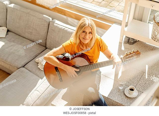 Woman at home playing guitar