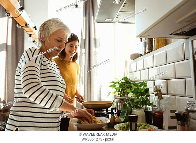 Senior woman and daughter preparing salad