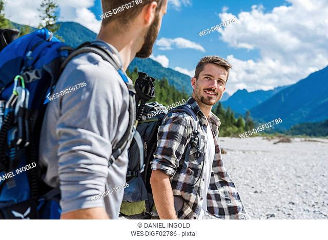 Germany, Bavaria, portrait of young hiker with backpack looking at his friend