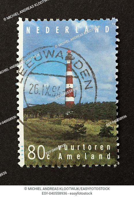HOLLAND - CIRCA 1990: Stamp printed in the Netherlands shows the lighthouse of the isle of Ameland, circa 1990