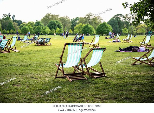 People sitting on deck chairs, Hyde Park, London, UK