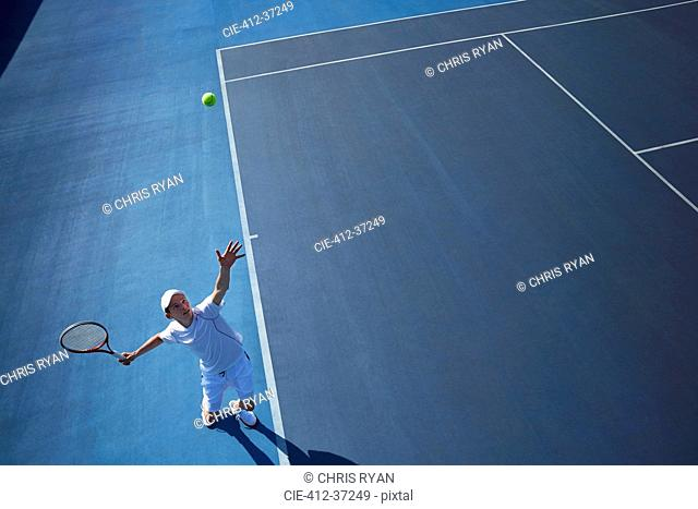Overhead view young male tennis player playing tennis, serving the ball on sunny blue tennis court