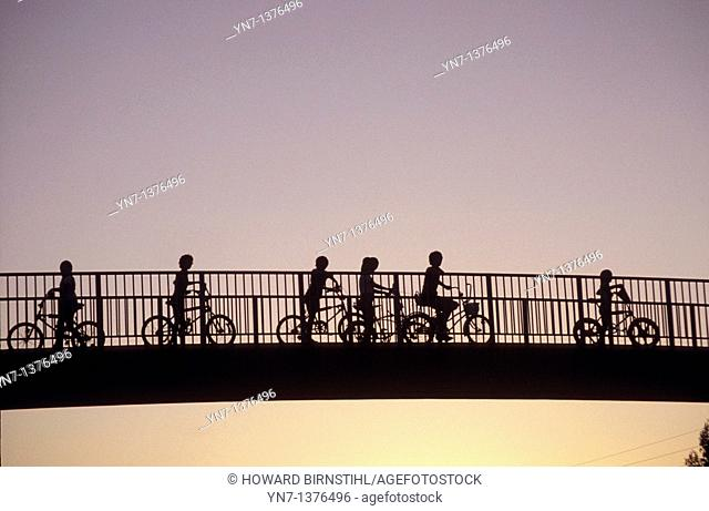 Abstract view of kids on bikes on a traffic overpass silhouetted against the evening sky