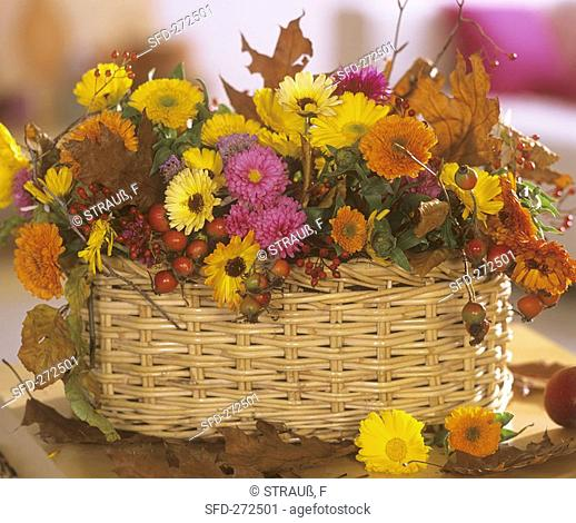Basket of rose hips, marigolds and chrysanthemums