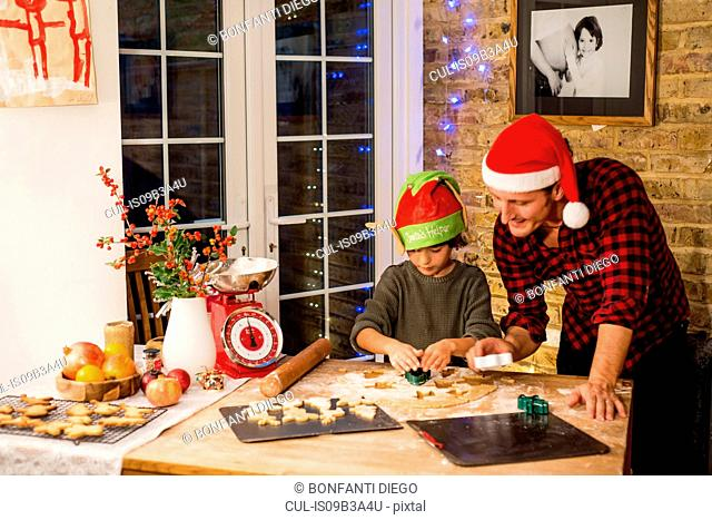 Man and son preparing Christmas cookies at kitchen counter