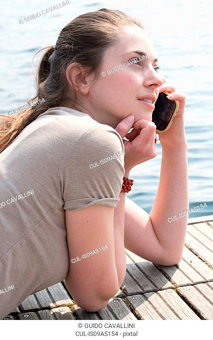 Young woman lying on pier chatting on smartphone, Lake Mergozzo, Verbania, Piemonte, Italy