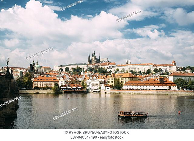 Prague, Czech Republic. Sightseeing Boat Sailing Along Vltava River On Background Upper Town. Prague Castle And Metropolitan Cathedral Of Sts Vitus