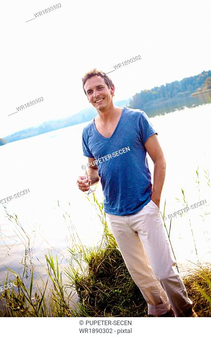 Mid adult man standing on the lakeside, drinking champagne, Bavria, Germany